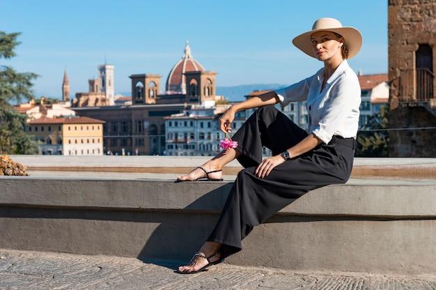 Portret van een charmant meisje, zittend in de buurt van een fontein in florence. uitzicht op santa maria del fiore. italië.