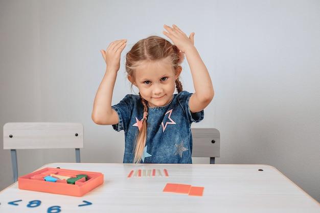 Portret van een charmant schattig en vrolijk meisje, zittend aan een witte tafel omringd door puzzels en haar handen opheffen van opwinding. jeugd concept. foto met ruis