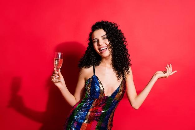 Portret van een charmant, vrolijk meisje met golvend haar dat plezier heeft met het drinken van wijnrust geïsoleerd op een felrode kleurachtergrond