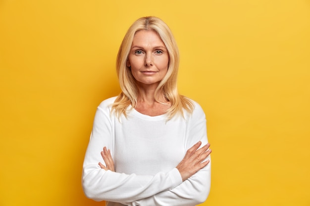 Portret van een charmante, aantrekkelijke vrouw van middelbare leeftijd met blond haar