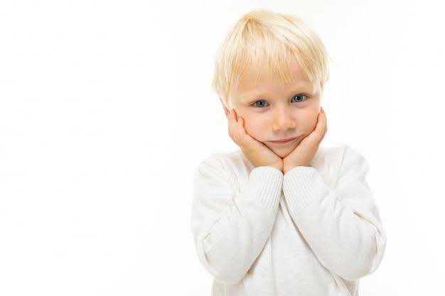 Portret van een charmante bescheiden blonde jongen in een wit t-shirt op een witte muur