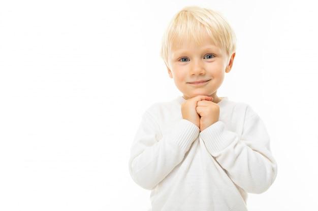 Portret van een charmante blonde jongen in een wit t-shirt op een witte muur