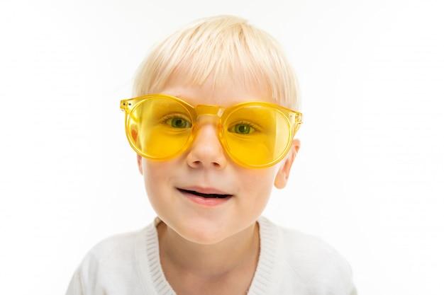 Portret van een charmante blonde jongen in zonnebril gekleed in een wit t-shirt op een witte muur