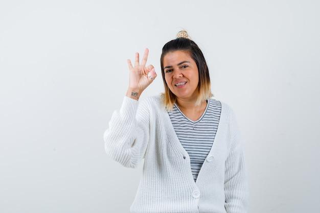Portret van een charmante dame die een goed gebaar toont in t-shirt, vest en er gelukkig uitziet