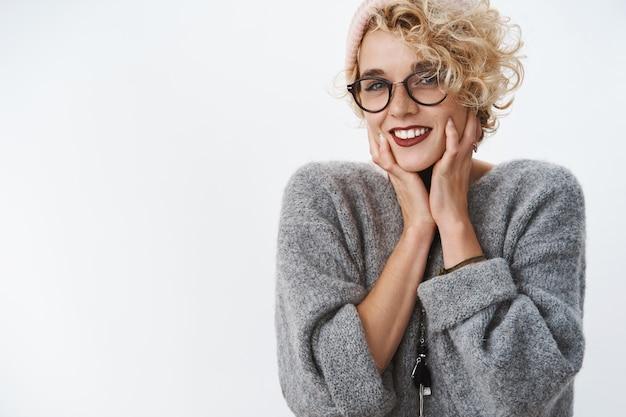 Portret van een charmante en tedere europese vrouw in een gezellige trui en een bril die haar gezicht zachtjes aanraakt en zich sensueel en zacht voelt poseren verrukt over de witte muur
