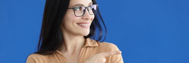 Portret van een charmante glimlachende vrouw die een richtingsgebaar toont