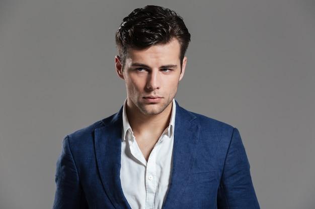 Portret van een charmante jonge man in jas