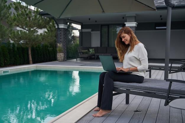 Portret van een charmante jonge vrouw die aan de chaise longue zit met een laptop en aan het werk is