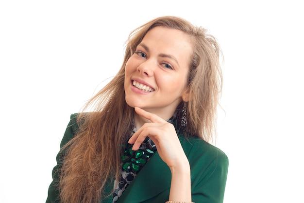 Portret van een charmante jonge vrouw die lacht en kijkt naar een camera geïsoleerd op een witte muur close-up