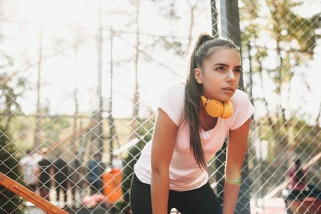 Portret van een charmante jonge vrouw die rijdt na het doen van cardio in de ochtend tijdens het luisteren naar mijmeren buiten in een sportpark.