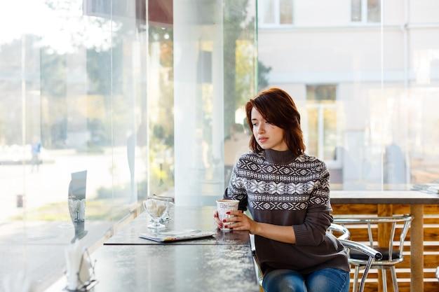 Portret van een charmante jonge vrouw met een vriendelijke glimlach brunette in een gebreide trui glimlachend naar haar