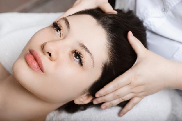 Portret van een charmante jonge vrouw met gezichtsprocedures in een wellness-kuuroord close-up.