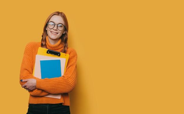 Portret van een charmante jonge vrouwelijke student met sproeten en rood haar die zonnebril dragen die camera glimlachen bekijken terwijl zijn boeken op geel worden geïsoleerd.