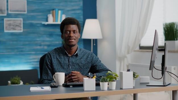 Portret van een charmante, knappe afro-amerikaanse man die lacht naar de camera