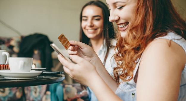 Portret van een charmante plus size vrouw die een smartphone en een gouden creditcard gebruikt die lacht terwijl ze in een restaurant zit. =