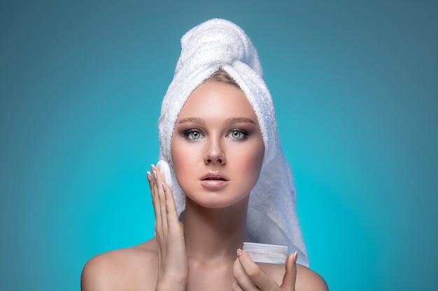 Portret van een charmante verrast vrouw met blauwe ogen met een handdoek op haar hoofd