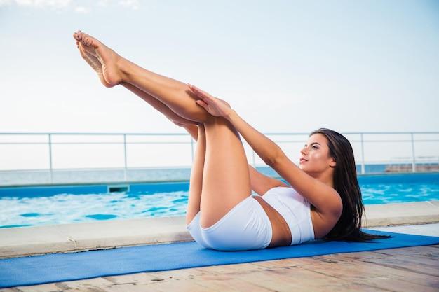 Portret van een charmante vrouw die zich uitstrekt op yoga mat buiten in de ochtend