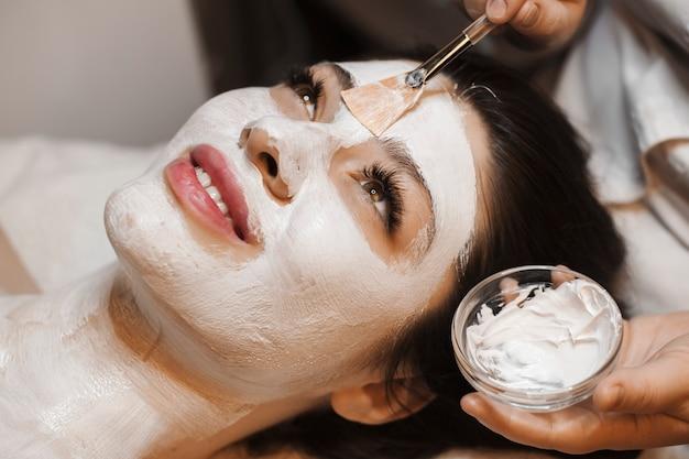 Portret van een charmante vrouw doet een wit gezichtsmasker in een wellnes spa close-up.