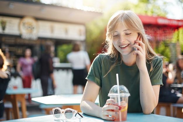 Portret van een chique jongedame praten met haar vriendje op smartphone limonade bedrijf in de middag in park op food court.