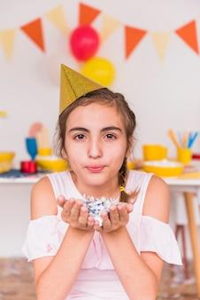 Portret van een confetti van de meisjesholding ter beschikking klaar te blazen