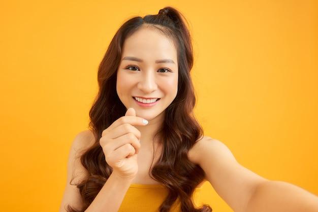 Portret van een cool, vrolijk meisje dat een smartphone in de hand houdt en een selfie maakt die geïsoleerd is op een oranje achtergrond en geniet van een weekendvakantie