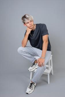 Portret van een coole tiener die zich voordeed op een stoel
