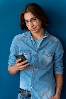 Portret van een coole tiener die zijn telefoon controleert