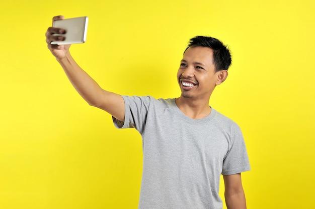 Portret van een coole vrolijke aziatische man die een videogesprek heeft met een minnaar die een smartphone in de hand houdt en een selfie maakt op de camera aan de voorkant, geïsoleerd op een gele achtergrond