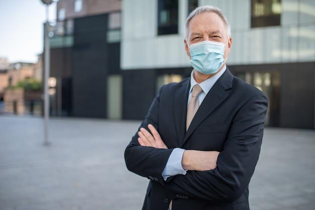 Portret van een covid coronavirus gemaskerde zakenman, managementconcept