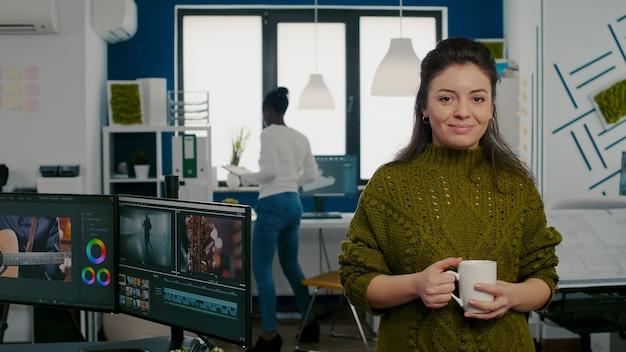 Portret van een creatieve ontwerper die lacht naar de camera en een kopje koffie vasthoudt in het kantoor van een startbureau