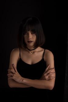 Portret van een dame in donkere toon, aziatische vrouw op zwarte achtergrond