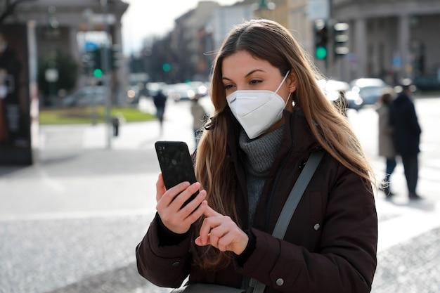 Portret van een dame in winterkleren en ffp2 kn95 gezichtsmasker wandelen in stad straat typen op smartphone