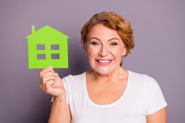 Portret van een dame in wit t-shirt met papieren huis geïsoleerd op paars