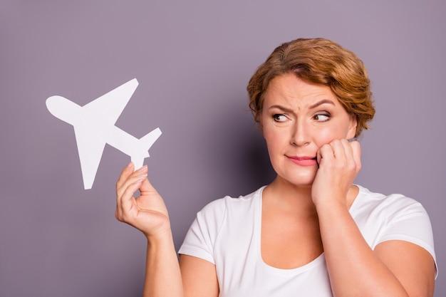 Portret van een dame in wit t-shirt met papieren vliegtuigje geïsoleerd op paars