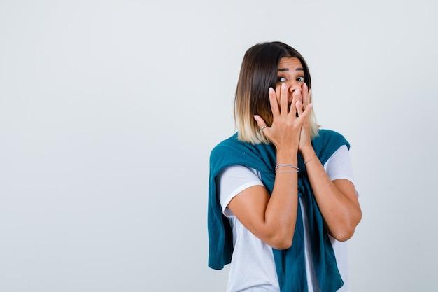 Portret van een dame met vastgebonden trui die de mond bedekt met handen in een wit t-shirt en er bang uitziet vooraanzicht
