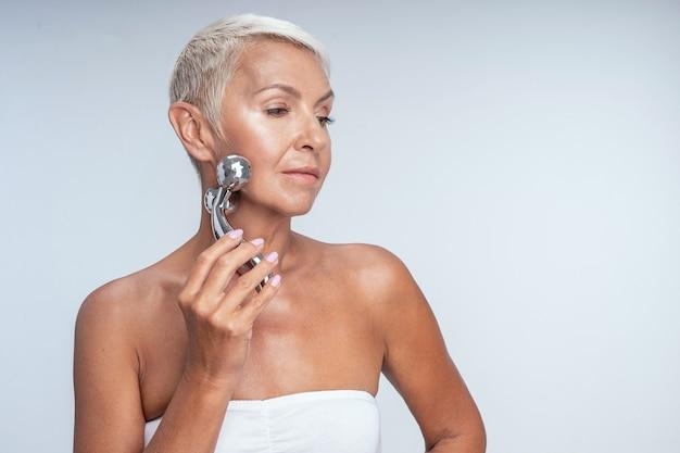 Portret van een dame van middelbare leeftijd die naar de zijkant kijkt en een gezichtsmassageapparaat tegen haar gezicht houdt