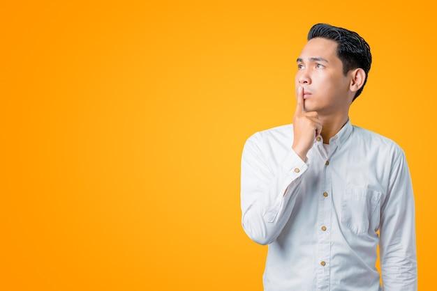Portret van een denkende aziatische man en omhoog kijkend met een vinger op de lippen