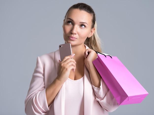 Portret van een denkende vrouw met roze boodschappentas en mobiele telefoon.