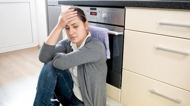 Portret van een depressieve en verdrietige eenzame vrouw die thuis in de keuken zit.