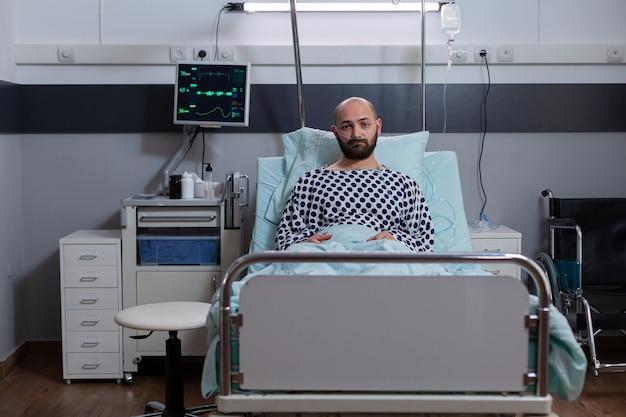 Portret van een depressieve zieke man die in bed ligt te wachten op ademhalingsbehandeling die herstelt na een medische ingreep op de ziekenhuisafdeling