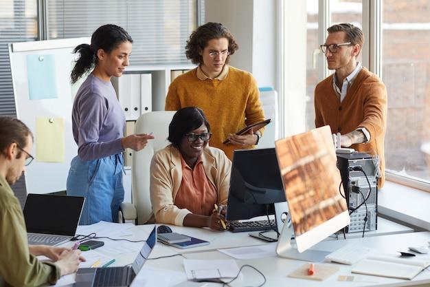 Portret van een divers it-ontwikkelingsteam dat samen een computer gebruikt tijdens het werken in een softwareproductiestudio