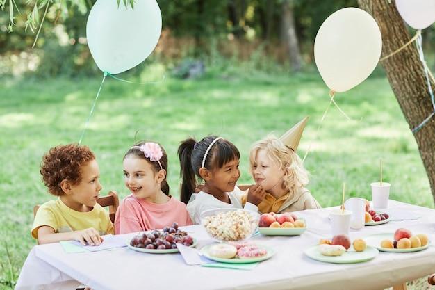 Portret van een diverse groep kinderen aan een picknicktafel die buiten geniet van een verjaardagsfeestje in de zomer