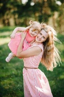 Portret van een dochter die moeder knuffelt op de natuur op zomervakantie. moeder en meisje spelen in het park bij zonsondergang. concept van vriendelijke familie. detailopname.