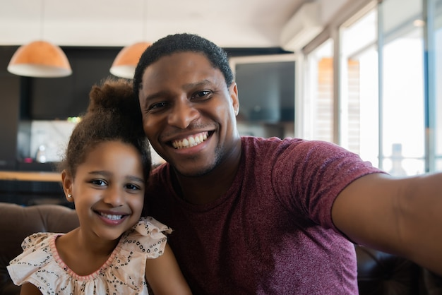 Portret van een dochter en vader die samen plezier hebben en een selfie maken terwijl ze op de bank thuis zitten