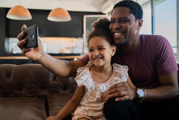 Portret van een dochter en vader die samen plezier hebben en thuis een selfie met mobiele telefoon nemen. monoparentaal concept.