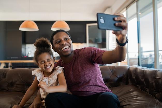 Portret van een dochter en vader die samen plezier hebben en thuis een selfie met mobiele telefoon nemen