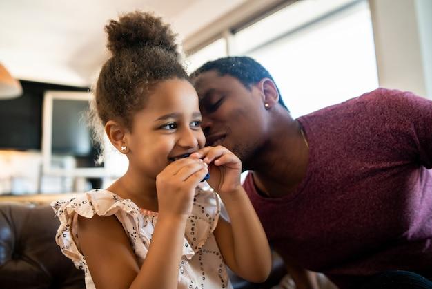 Portret van een dochter en vader die samen plezier hebben en thuis met ballons spelen. monoparentaal concept.
