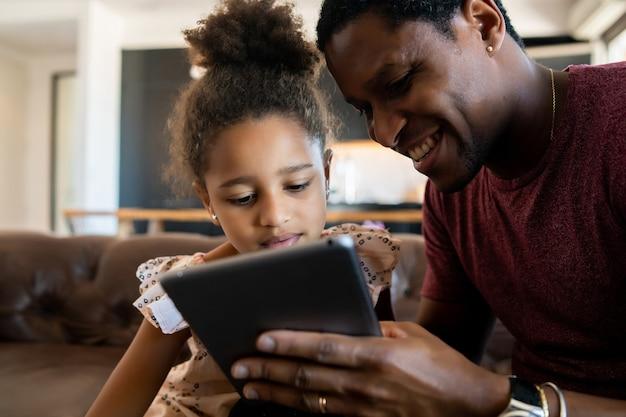 Portret van een dochter en vader die samen plezier hebben en thuis met digitale tablet spelen. monoparentaal concept.