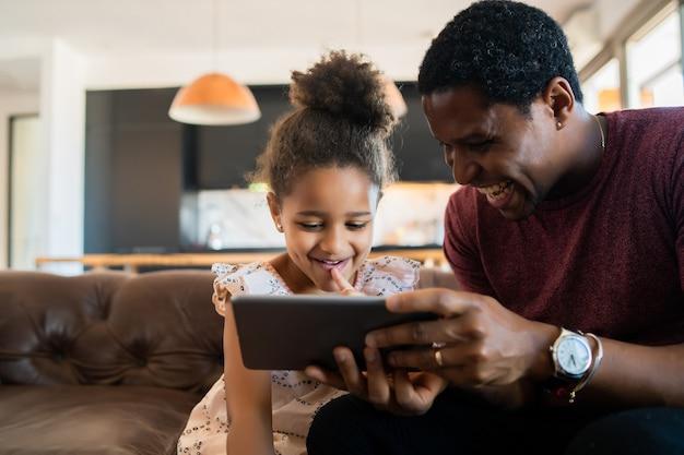 Portret van een dochter en vader die samen plezier hebben en thuis met digitale tablet spelen