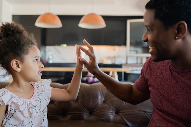 Portret van een dochter en vader die thuis samen plezier hebben